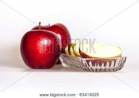 Two ripe red apples and segments of apple on a plate