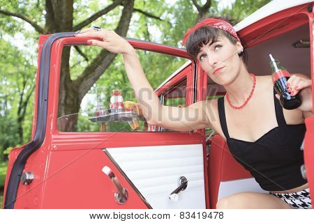 A retro girl with a beautiful red old car.