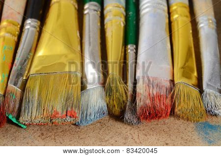Artist's Desktop With Old Dirty Colourful Brushes On Wood Background