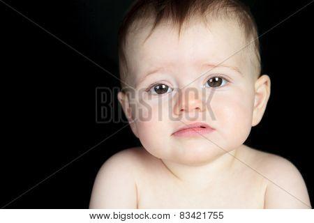 Sweet little boy sitting on studio black background