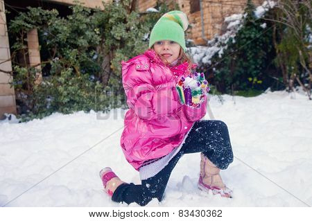 Blonde Girl Standing On One Knee With Snowball