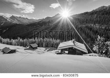 Sunrise over the ski huts in black and white