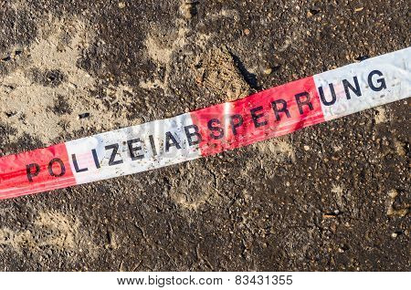 German Police Line Red White Tape On Street Asphalt Dirt