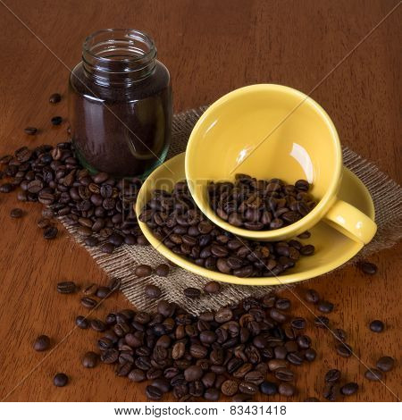 Cup with saucer, pot with coffee and coffee beans on the table