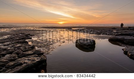 Sunset over a calm rock pool on a UK Beach