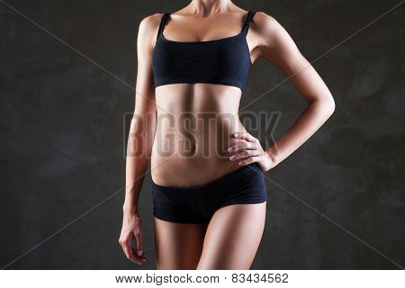 Slim woman's body  over dark grey background