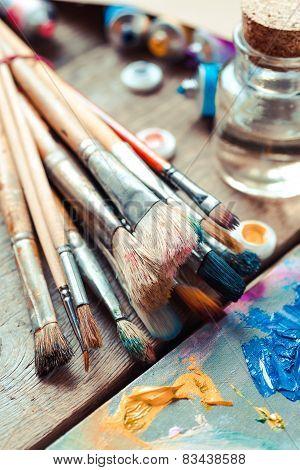 Vintage Stylized Photo Of Paintbrushes Closeup, Artist Palette And Multicolor Paint Tubes.