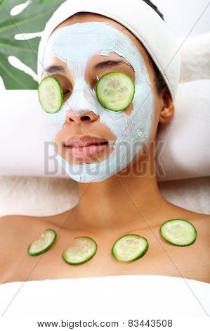 Cosmetic procedure woman's face in the mask mitigating and cucumber slices on eyes
