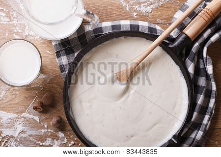 Bechamel Sauce In A Pan And Milk On The Table Top View