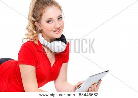 Young woman enjoying music on headphones using digital tablet while lying on the floor at home