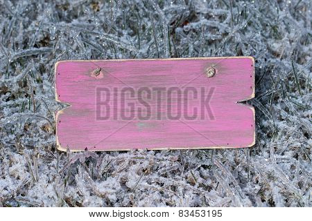 Blank pink wooden sign with ice covered grass background