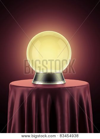 Yellow magic globe on table covered with red cloth