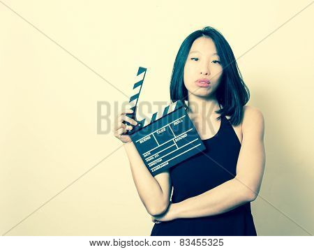 Young Beautiful Asian Woman With Clapperboard Vintage Colors Portrait