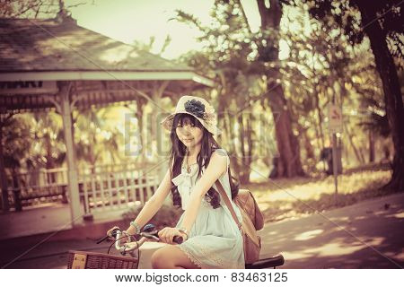 Cute Asian Thai girl in vintage clothing is riding a bicycle, in the sunny summer park.