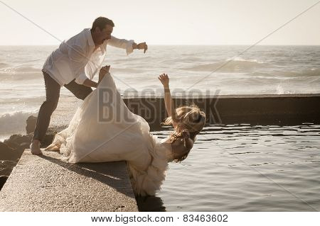 Young beautiful bridal couple having fun together at the beach