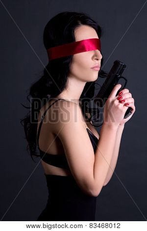 Young Beautiful Sexy Woman In Black Lingerie With Red Ribbon On Eyes Holding Gun Over Grey