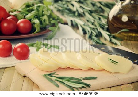 Tinted Image Sliced Cheese, Tomatoes And Herbs On A Kitchen Table Closeup