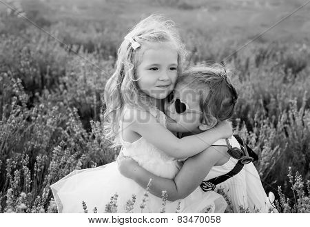two little girls hugging on a lavender