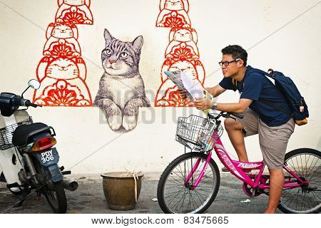 Malaysia, Penang, Georgetown - Circa Jul 2014: A Tourist On A Bicycle Stops To Examine His Map In Fr