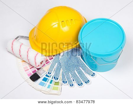 Painter's Tools - Brushes, Work Gloves, Helmet And Bucket Of Blue Paint Over White