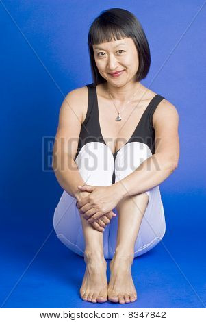 Asian Woman with Short Hair Sitting and Smiling