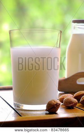 Glass Of Almond Milk On A Table With Almonds Front View Closeup