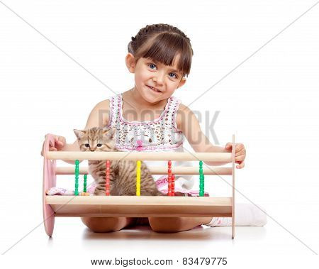 child playing with a kitten and rocking him in doll crib