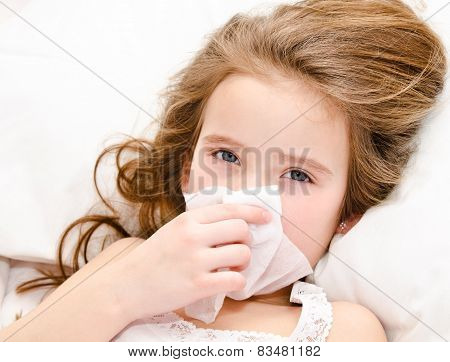Little Girl Lying In The Bed And Blowing Her Nose