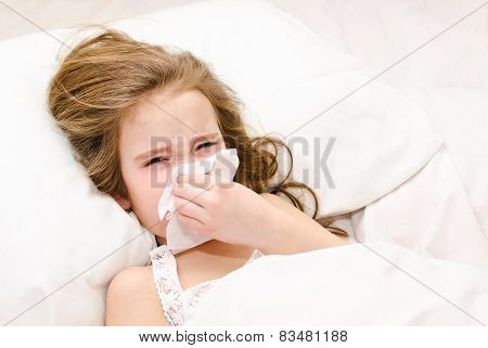 Little Girl Lying In The Bed Blowing Her Nose