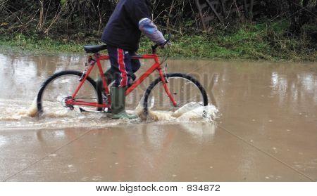 boy cycling through flood