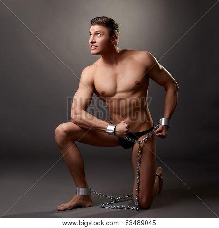 Sexy bodybuilder posing in handcuffs