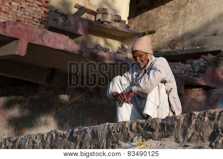 Indian Man Sits On A Ghat At The River Ganga