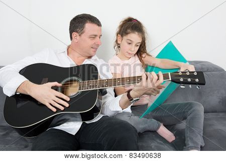 Father And Daughter During A Guitar Lesson.