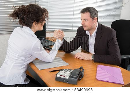 Business Couple Arm Wrestling At The Office