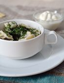 pic of greenery  - closeup of traditional russian pelmeni in a bowl with greenery butter and sour cream - JPG