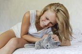 picture of caress  - Young beautiful woman caressing british cat on the bed - JPG