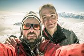 stock photo of italian alps  - Adult european men taking selfie on the mountain summit with snowcapped italian Alps in background - JPG