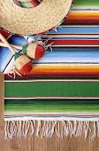 stock photo of maracas  - Mexican background with sombrero straw hat maracas and traditional serape blanket or rug on a wood floor - JPG