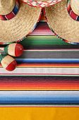 picture of maracas  - Mexican background with sombrero straw hat maracas and traditional serape blanket or rug - JPG