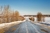stock photo of slippery-roads  - winter slippery road with turns going into horizon - JPG