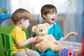 pic of home remedy  - children brothers play doctor with plush toy at home - JPG