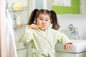 picture of teeth  - Smiling child girl brushing teeth in bathroom - JPG