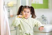 stock photo of tooth  - Smiling child girl brushing teeth in bathroom - JPG