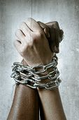 stock photo of chains  - white Caucasian hand chained with iron chain and locked together with black ethnicity female around wrists in togetherness multiracial respect and understanding concept - JPG