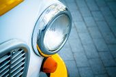 stock photo of headlight  - Headlight of the old car on a background of paving stones - JPG