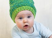 picture of knitted cap  - Infant toddler boy lies in a green knitted cap - JPG