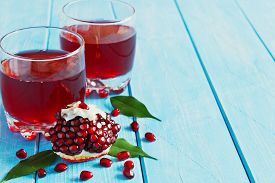 stock photo of seed  - ripe pomegranate seeds and fresh pomegranate juice on a blue wooden background - JPG