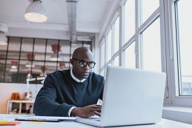 picture of candid  - Shot of a bald african businessman working on laptop computer in office - JPG