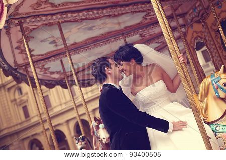 Bride and groom kissing on carousel