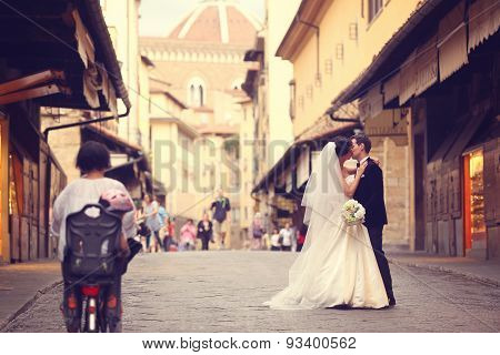 Happy bridal couple embracing in street